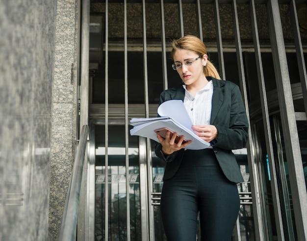 Blonde junge geschäftsfrau, die gegen den eingang steht, der dokument überprüft