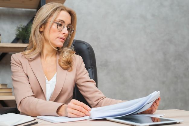 Blonde junge geschäftsfrau, welche die dokumente am arbeitsplatz liest