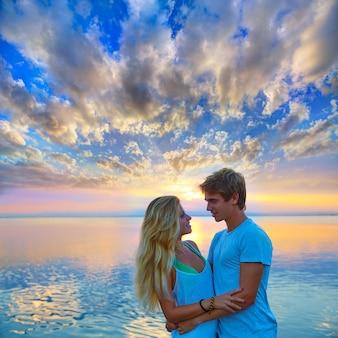 Blonde junge paare umarmen im sonnenuntergangseesee glücklich