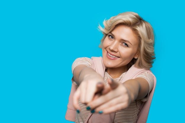 Blonde kaukasische dame, die auf die kamera zeigt, während auf einer blauen wand mit kopienraum lächelt