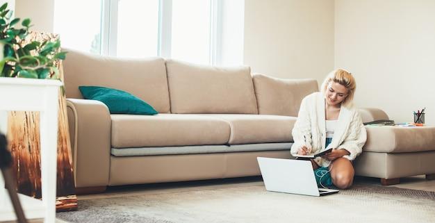 Blonde kaukasische frau, die auf boden sitzt und notizen macht, während sie den laptop betrachtet