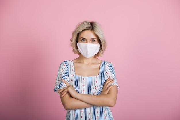 Blonde kaukasische frau, die eine medizinische maske und ein kleid trägt, betrachtet kamera auf einer rosa studiowand