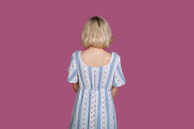 Blonde kaukasische frau, die zum lila hintergrund schaut, während sie ein kleid trägt
