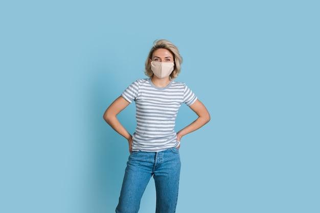 Blonde kaukasische frau mit einer medizinischen maske, die auf einer blauen studiowand in den jeans und im hemd aufwirft