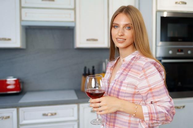 Blonde kaukasische frau mit glas rotwein, der in ihrer küche steht