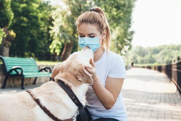 Blonde kaukasische frau mit medizinischer maske auf gesicht, das im park mit einem labrador geht, der es küsst und umarmt