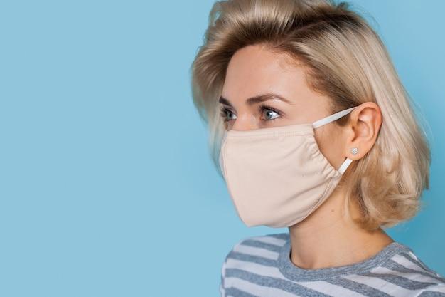 Blonde kaukasische frau mit medizinischer maske posiert auf einer blauen studiowand, die etwas annonciert