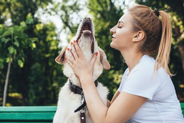 Blonde kaukasische frau spielt mit ihrem hund, der auf einer bank während eines spaziergangs im park sitzt.