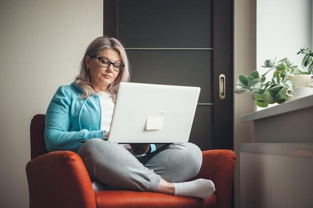 Blonde kaukasische gealterte frau mit brille, die im sessel am laptop ruht