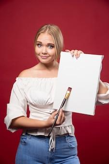 Blonde künstlerin, die ihre kunstwerke mit freudigem selbstvertrauen zeigt.