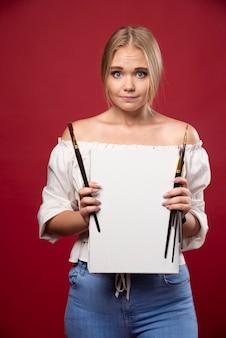 Blonde künstlerin, die zögernd ihre kunstwerke zeigt und nach rezensionen sucht.