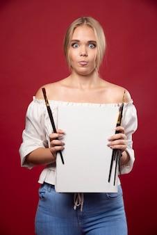 Blonde kunstmeisterin, die mit einem pinsel auf leinwand arbeitet und ihre kunstwerke zögernd zeigt.