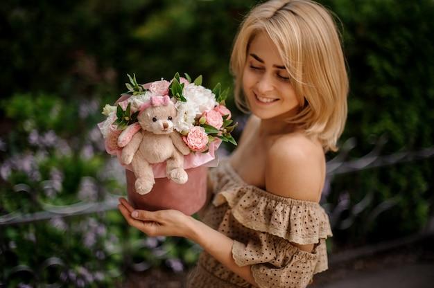 Blonde lächelnde frau, die eine box mit blumen gefüllt hält
