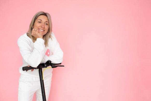 Blonde lächelnde frau, die glücklich ist, elektroroller zu kaufen, alternatives verkehrskonzept