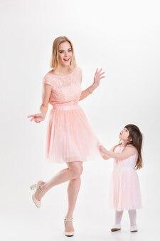 Blonde lächelnde mutter und süße kleine tochter in rosa prinzessinnenkleidern ziehen ihr kleid auf grauem hintergrund. familie