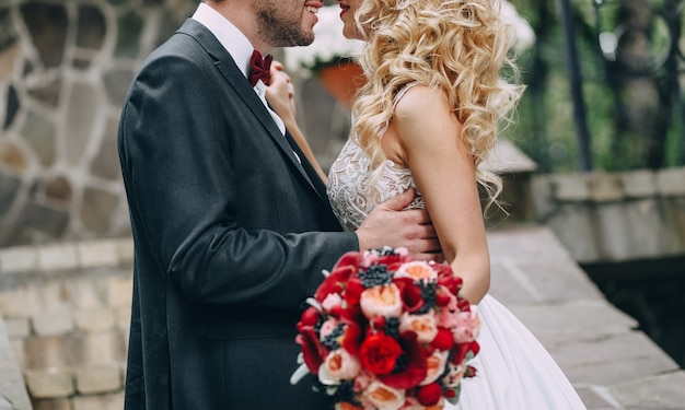 Blonde liebevolle paare der braut und des bräutigams, die draußen umarmen