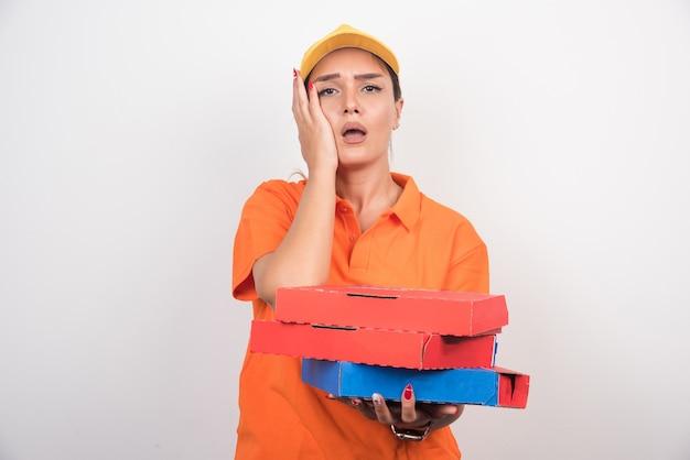 Blonde lieferfrau, die ihr gesicht und pizzaschachteln auf weißem hintergrund hält.