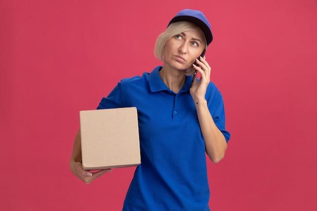 Blonde lieferfrau mittleren alters in blauer uniform und mütze mit pappkarton, die am telefon nach oben spricht