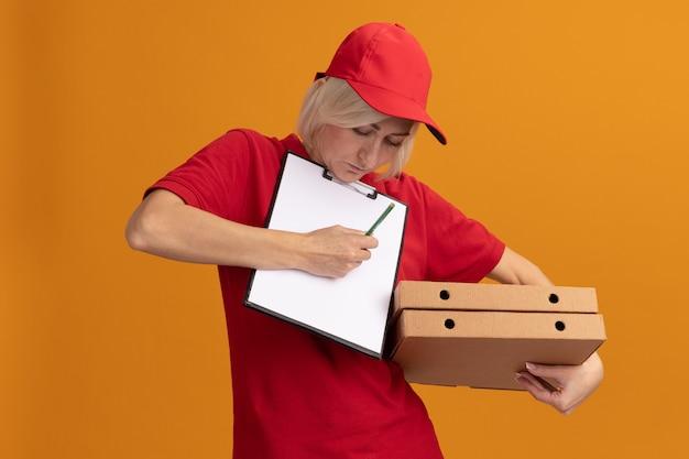 Blonde lieferfrau mittleren alters in roter uniform und mütze, die pizzapakete und zwischenablage unter dem kinn hält und auf zwischenablage mit bleistift isoliert auf oranger wand schreibt