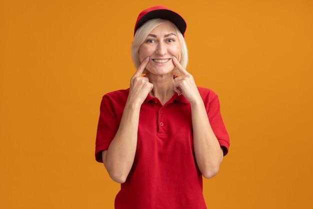 Blonde lieferfrau mittleren alters in roter uniform und mütze mit blick auf die vorderseite, die ein falsches lächeln isoliert auf der orangefarbenen wand mit kopienraum macht