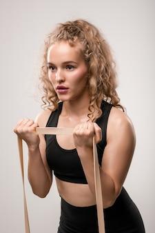 Blonde lockige sportlerin mit flexiblem band, die während des täglichen trainings im fitnessstudio oder zu hause körperliche bewegung für arme macht