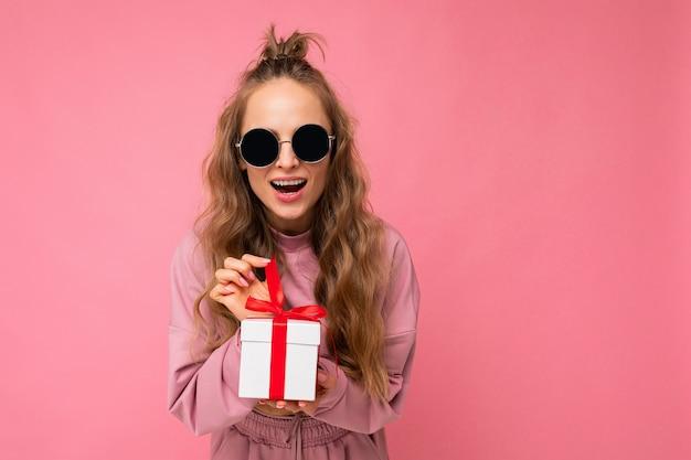 Blonde lockige weibliche person lokalisiert auf rosa hintergrundwand tragen