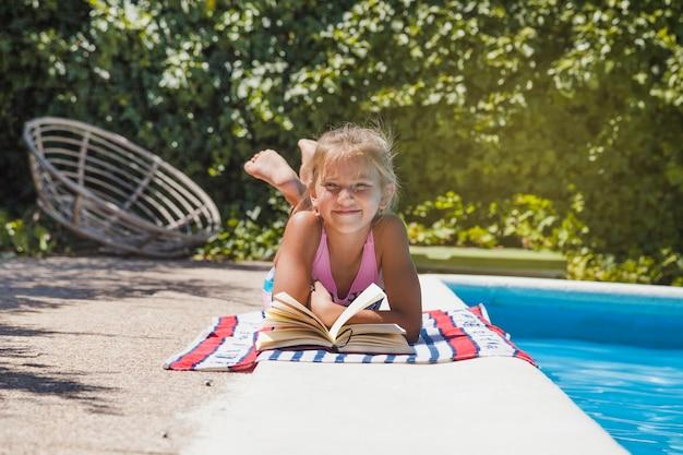 Blonde mädchen liegend am pool mit buch