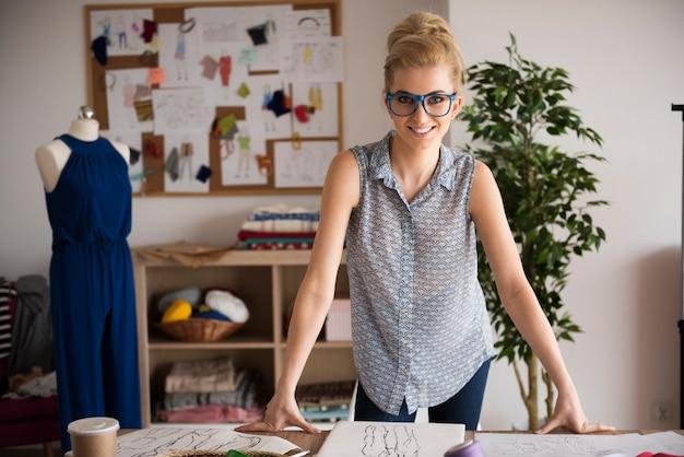 Blonde modedesignerin in ihrer werkstatt