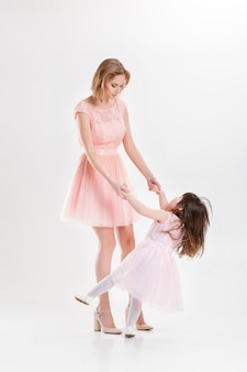 Blonde mutter und süße kleine tochter in rosa kleidern prinzessinnen, die auf grauem hintergrund umarmen und lachen. familie