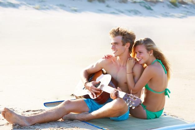 Blonde paare, die in einem strandsand spielt gitarre sitzen