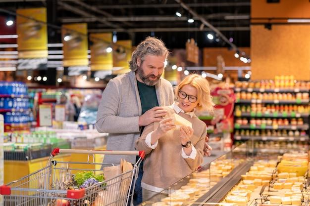 Blonde reife frau, die ein stück käse hält, während sie durch großes display steht und milchprodukte mit ihrem ehemann auswählt