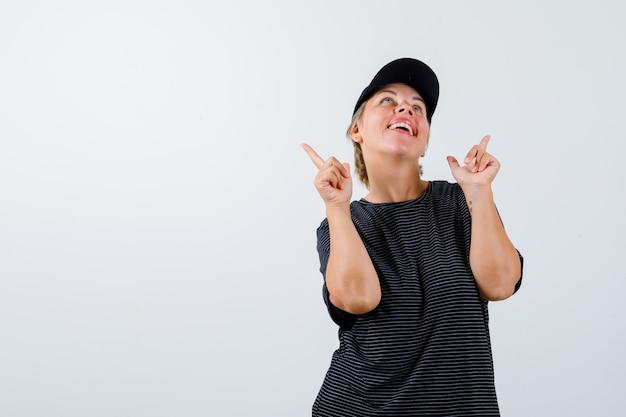 Blonde reife frau in einem schwarzen t-shirt und einer schwarzen mütze