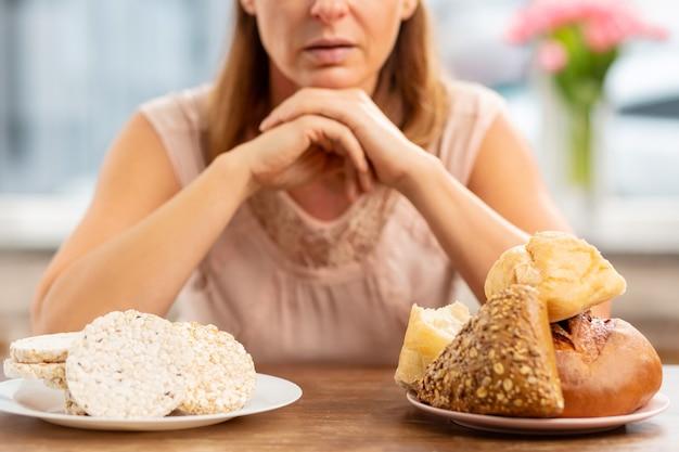 Blonde reife frau mit allergie, die sich zwischen chips und brot entscheidet