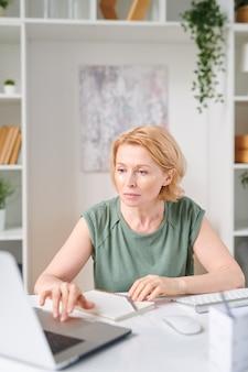 Blonde reife geschäftsfrau mit unter augenklappen, die vom schreibtisch vor laptop während der fernarbeit sitzen, während zu hause für quarantäne bleiben