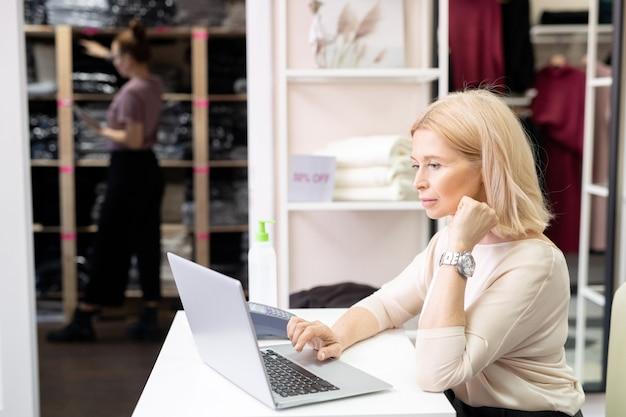 Blonde, reife, seriöse verkäuferin in smart casualwear, die am schreibtisch vor dem laptop sitzt und die online-liste des neuen sortiments durchsieht