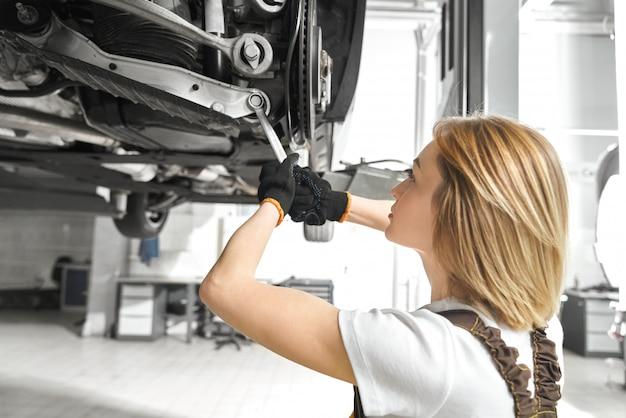 Blonde reparatur auto fahrwerk mit schraubenschlüssel.