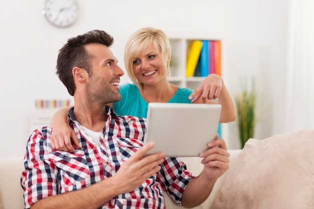 Blonde schöne frau, die etwas auf digitalem tablett zeigt