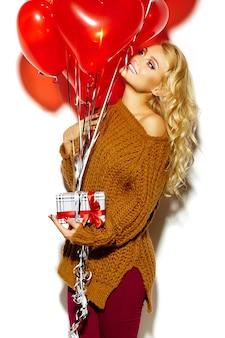 Blonde schöne frau im kuscheligen pullover, der geschenk und luftballons hält