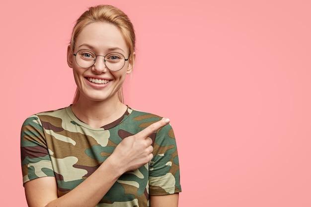 Blonde schöne frau mit positivem lächeln, zeigt weiße zähne, zeigt zur seite