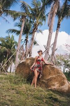 Blonde schönheit des reisenden in der sonnenbrille gehend in tropischen park des dschungels. reiseabenteuer-natur in china, touristischer schöner bestimmungsort asien, sommerferien-ferienreisereisekonzept