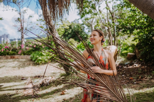 Blonde schönheit des reisenden mit dem palmblatt, das im tropischen park des dschungels aufwirft reiseabenteuer-natur in china, touristischer schöner bestimmungsort asien, sommerferien-ferienreisereisekonzept
