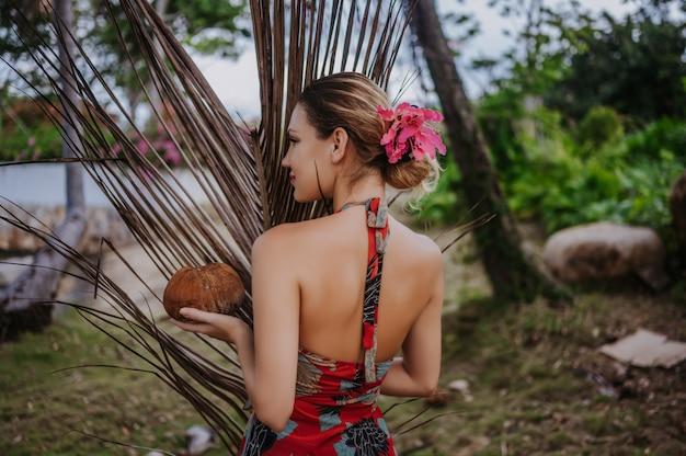 Blonde schönheit des reisenden mit der kokosnuss, die im tropischen park des dschungels aufwirft reiseabenteuer-natur in china, touristischer schöner bestimmungsort asien, sommerferien-urlaubsreise-reisekonzept