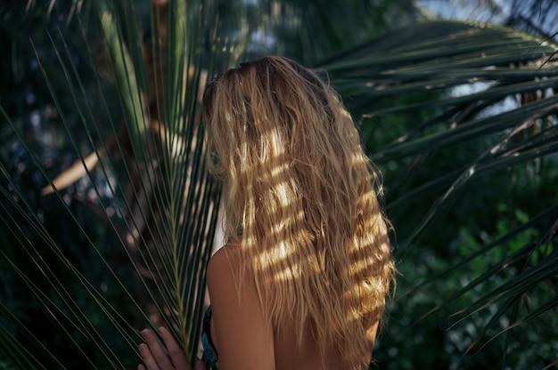 Blonde schönheit mit dem nassen haar, das in der tropischen parkrückseitenansicht des dschungels aufwirft. reiseabenteuer-natur in china, touristischer schöner bestimmungsort asien, sommerferien-ferienreisereisekonzept