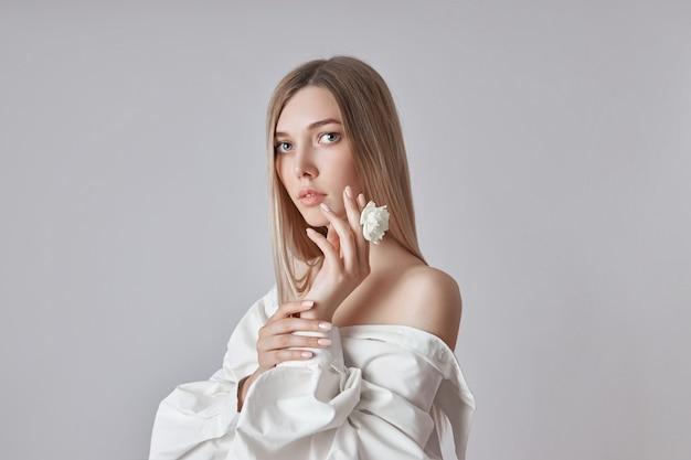 Blonde schönheitsfrau hält weiße blume in der hand. schöne weiche hände und weiche haut. kosmetik für die schönheit der handpflege