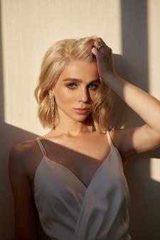 Blonde schönheitsfrau in einem weißen kleid steht in der abendsonne am fenster. porträt eines mädchens mit einem strauß wilder blumen, natürliches make-up