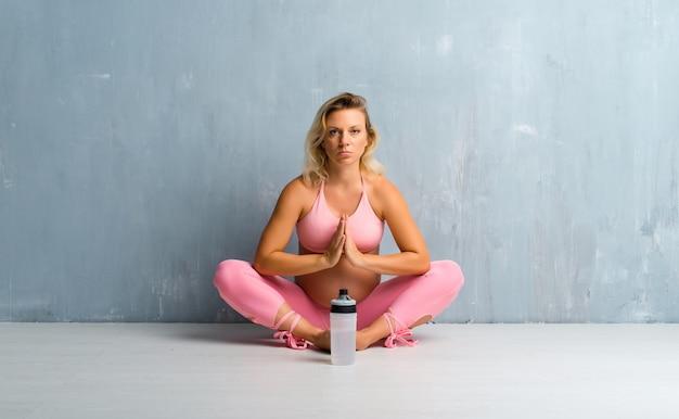 Blonde schwangere frau, die yoga tut
