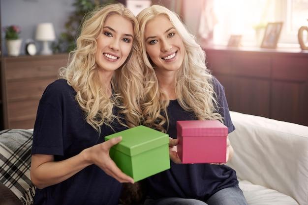 Blonde schwestern halten zwei kleine geschenk