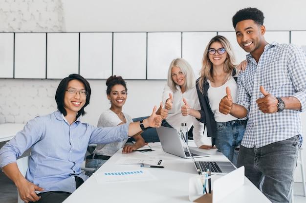 Blonde sekretärin sitzt auf tisch, während büroangestellte mit daumen hoch posieren. innenporträt des glücklichen asiatischen managers im trendigen hemd, das im konferenzsaal mit ausländischen partnern lächelt.