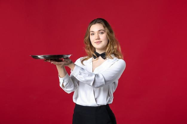 Blonde selbstbewusste weibliche serverschmetterling am hals und hält tablett auf rotem hintergrund