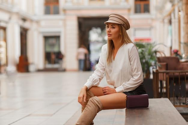 Blonde sexy europäische frau in der trendigen autun kappe, die draußen aufwirft
